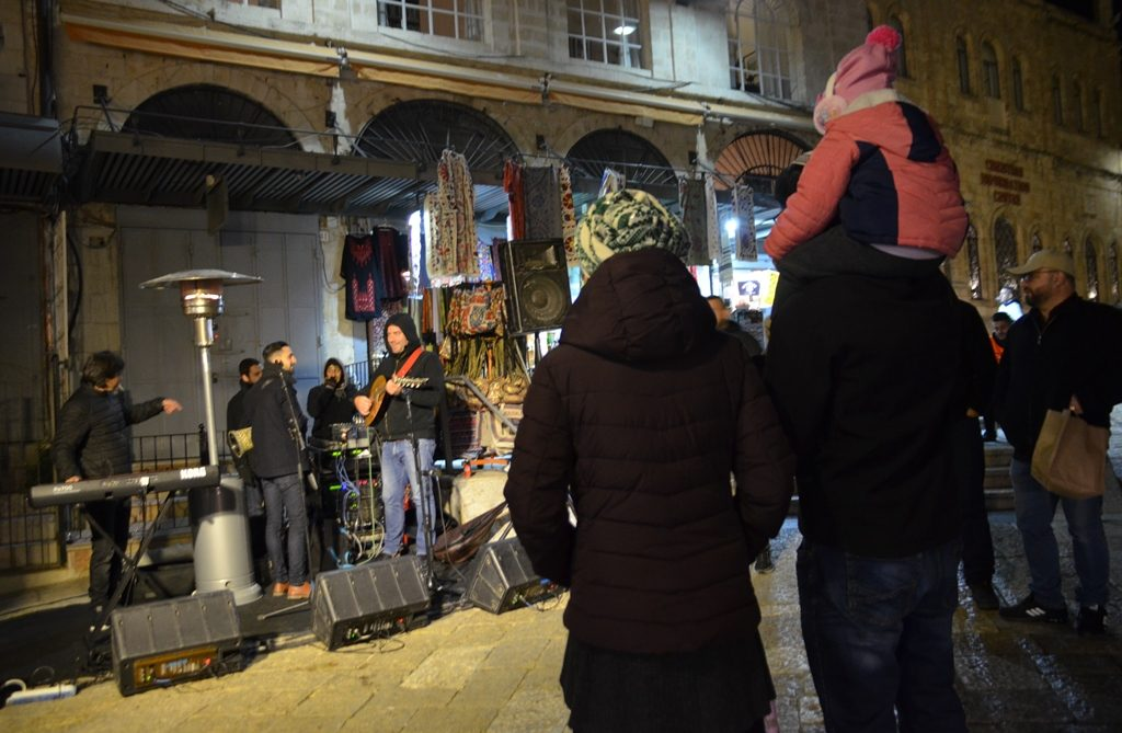 Young couple with child watching in Old City Jerusalem for Winter Noise festival