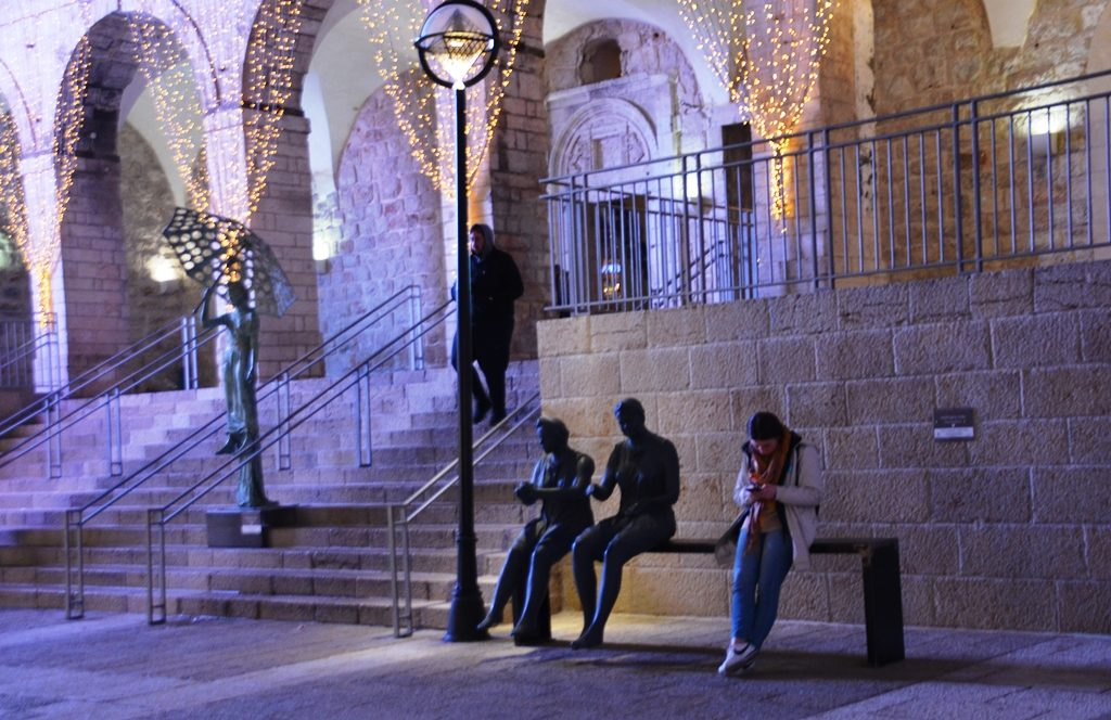 Jerusalem art work on Mamilla Mall at night young woman sitting on art piece