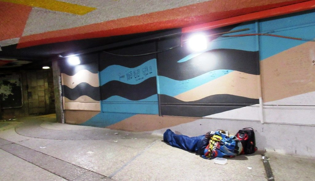 Near Jerusalem main bus station man sleeping in tunnel pass under street