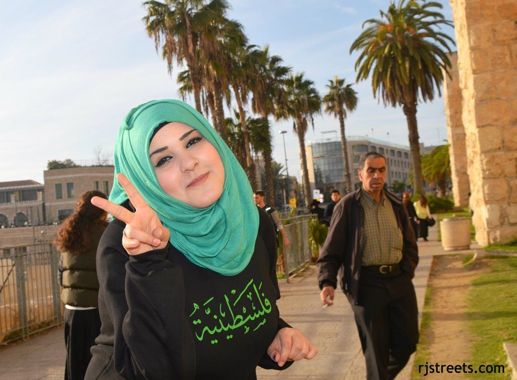 Girl wearing hijab and Arabic writing palestine sweatshirt near old city with fingers in V signal