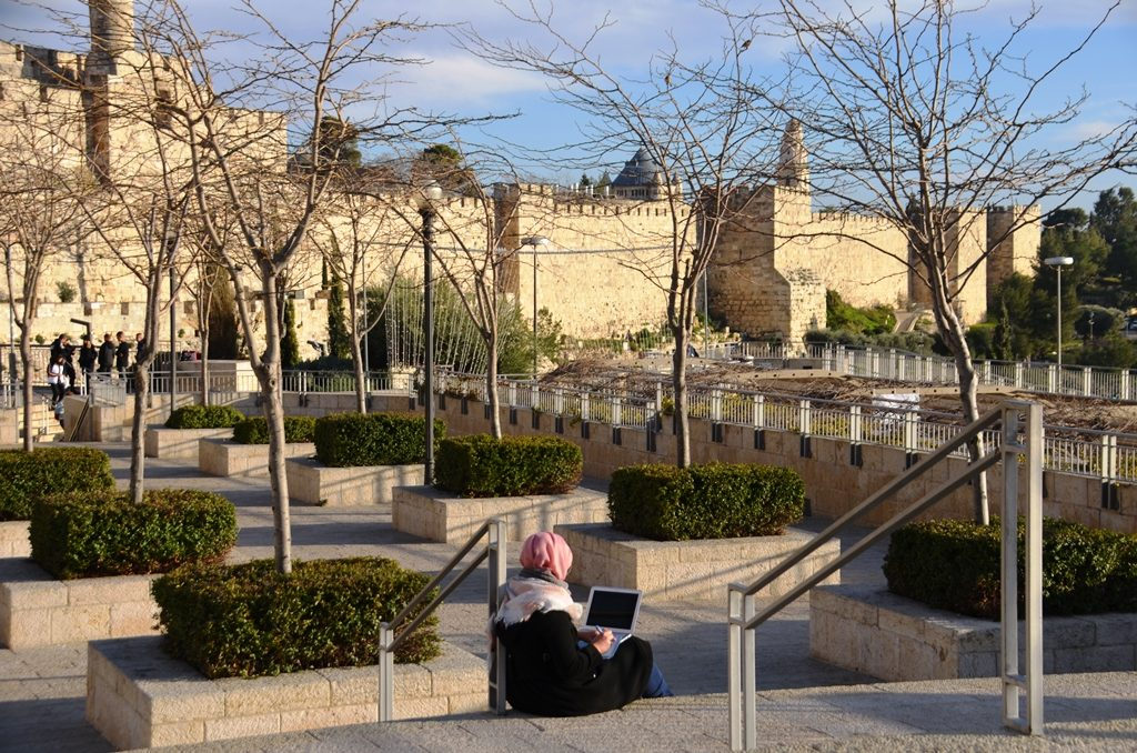 Muslim women in hijab using laptop near walls of Old City Jerusalem Israel
