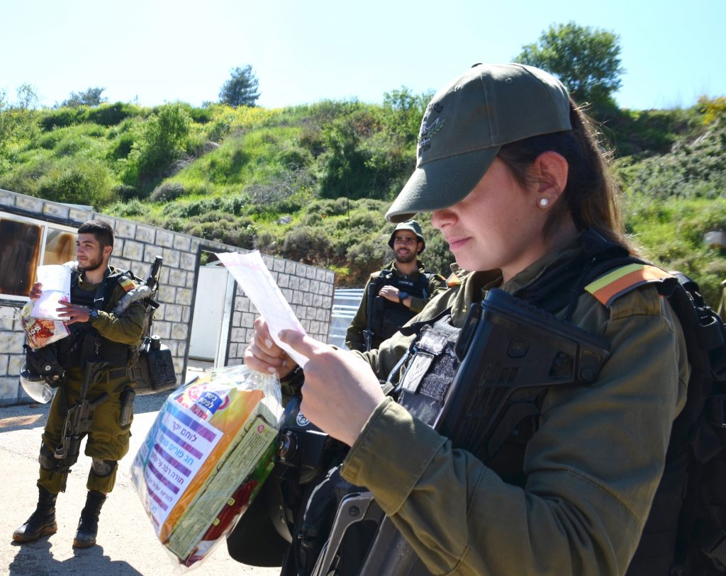 Female soldier reading letter from children and receiving Mishloah manot.