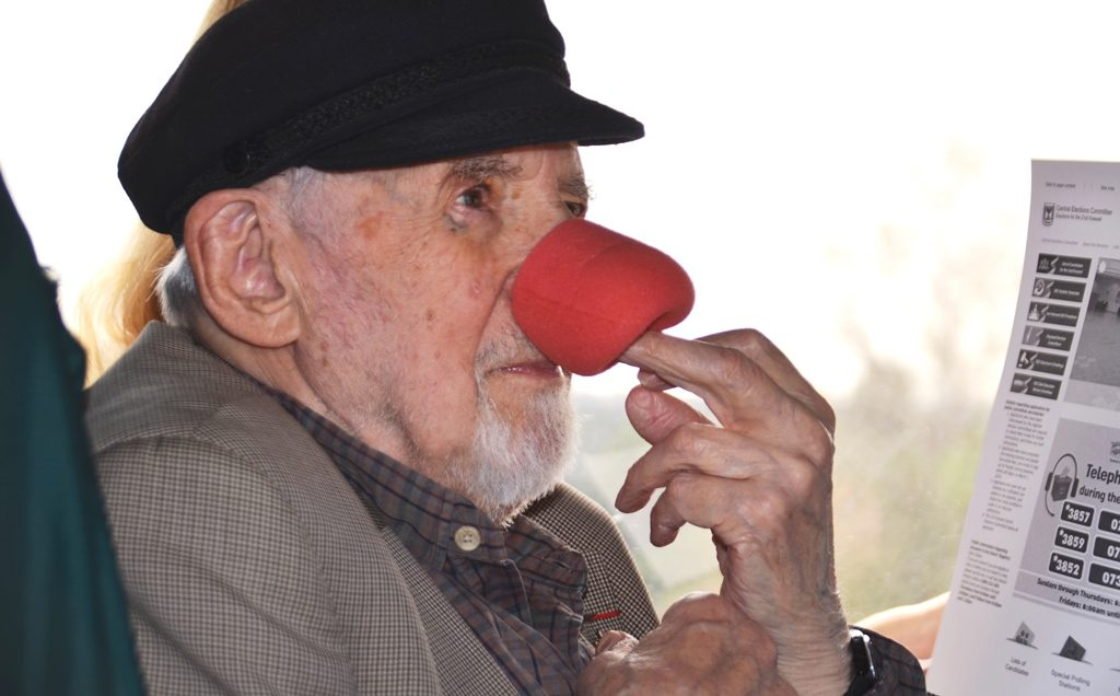 Man with microphone red on his nose as a clown