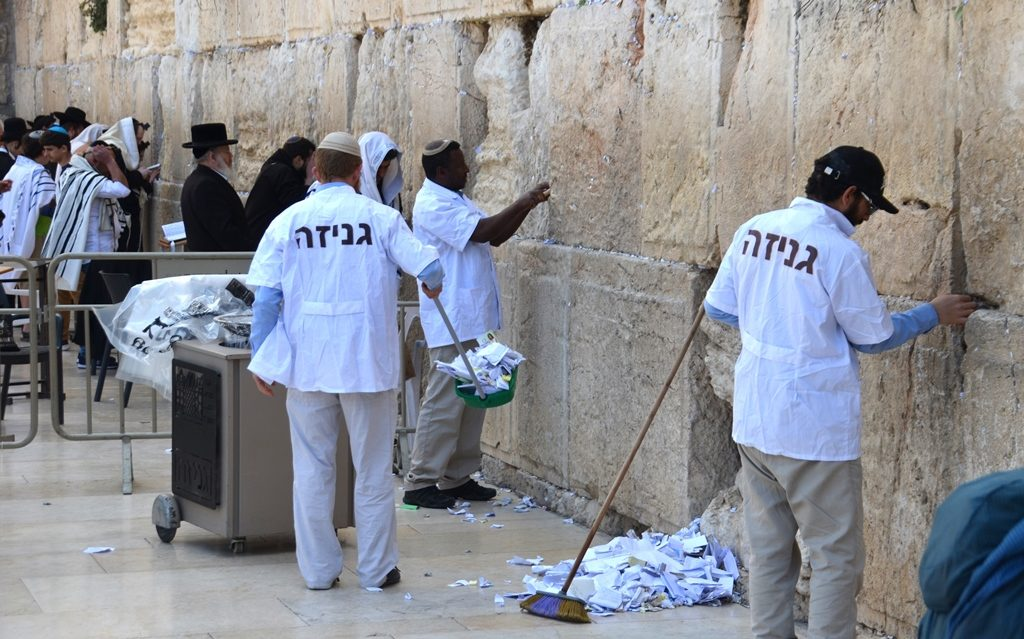 Men cleaning notes from Western Wall Kosel before Pesach