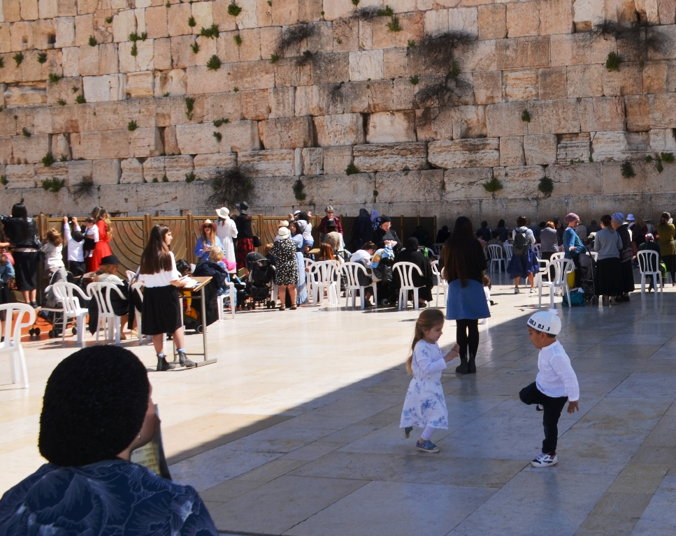 Kotel in women's section with a little girl and boy dancing.