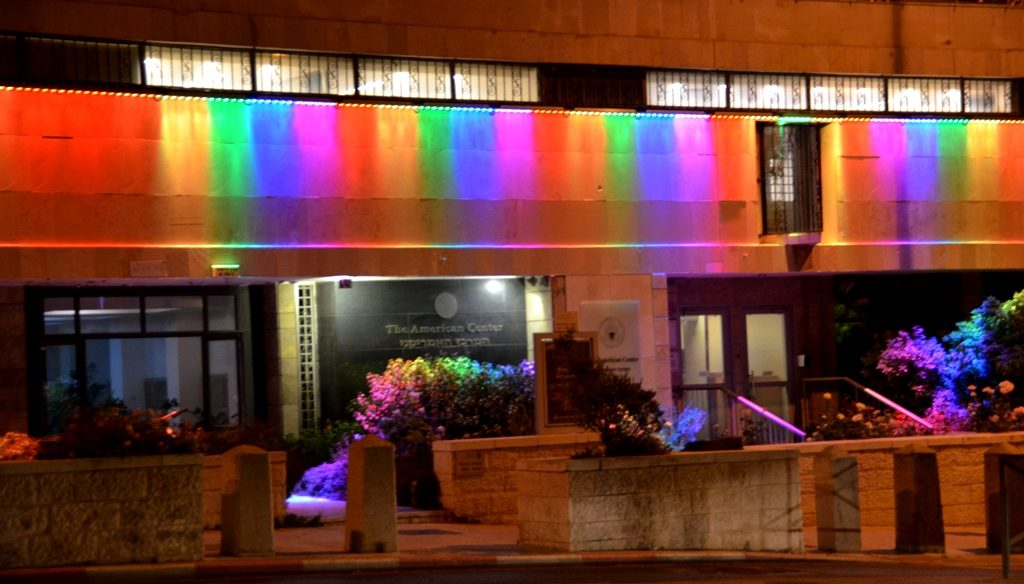 Jerusalem American Center lit at night with colorful lights, Gay Pride month
