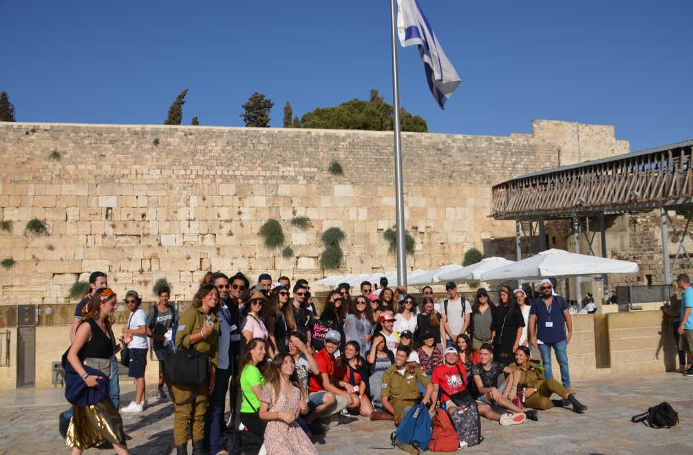 Young people on trip to Israel pose at Western Wall for group photo