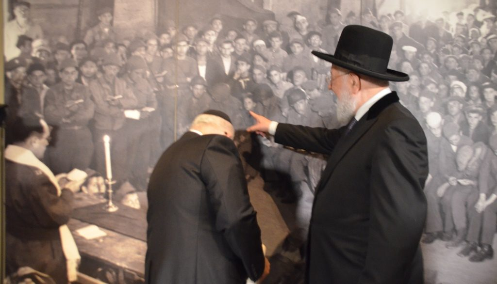 Rabbi Y M Lau pointing to himself as a child in large photo in Yad Vashem