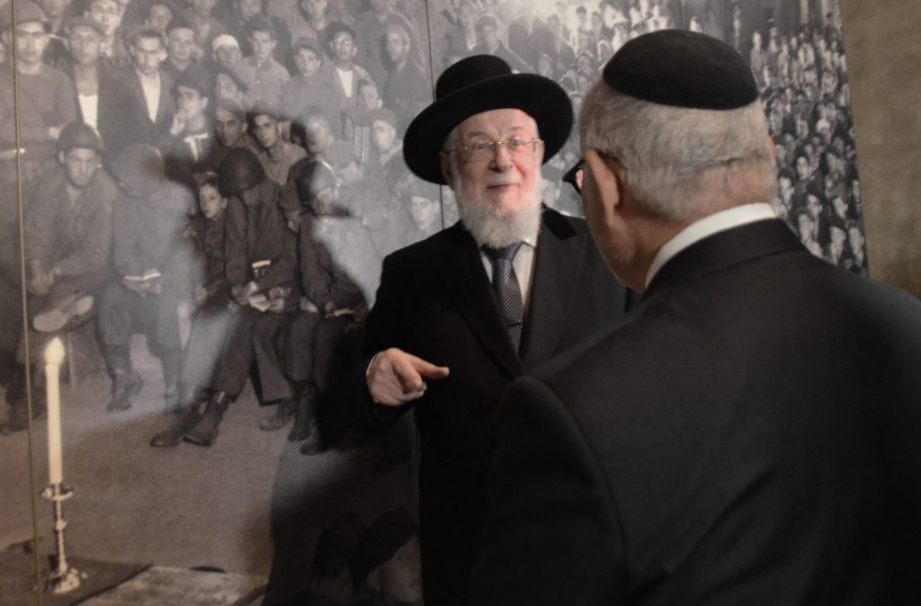 Rabbi Y M Lau at Yad Vashem near photo of himself as a child