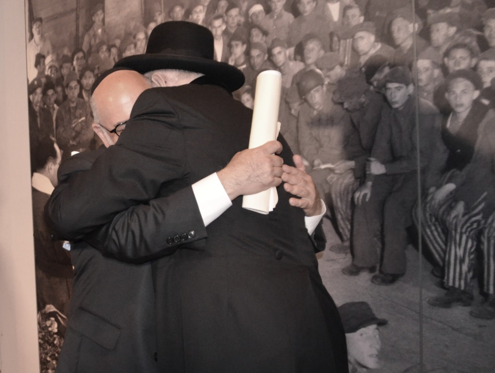Near photo of his father Rabbi JJ Schacter hugs Rabbi Y M Lau who was also in the image as a child after liberation