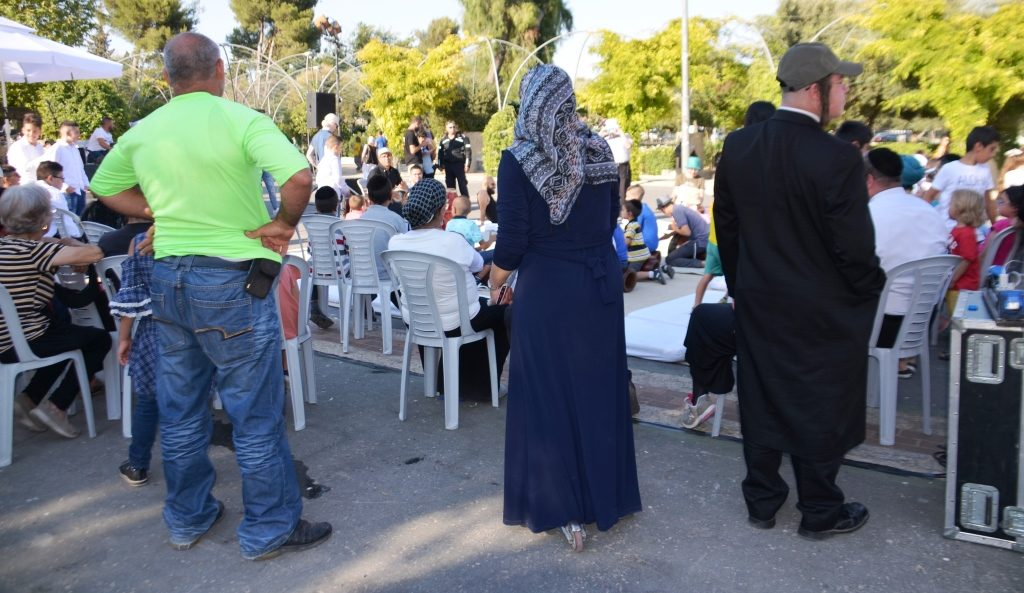 Muslim woman standing with Jewish man at music event in Liberty Bell Park Jerusalem
