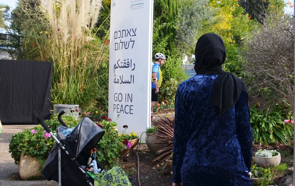 Muslim woman at ALYN hospital sign saying Go in Peace in Jerusalem Israel
