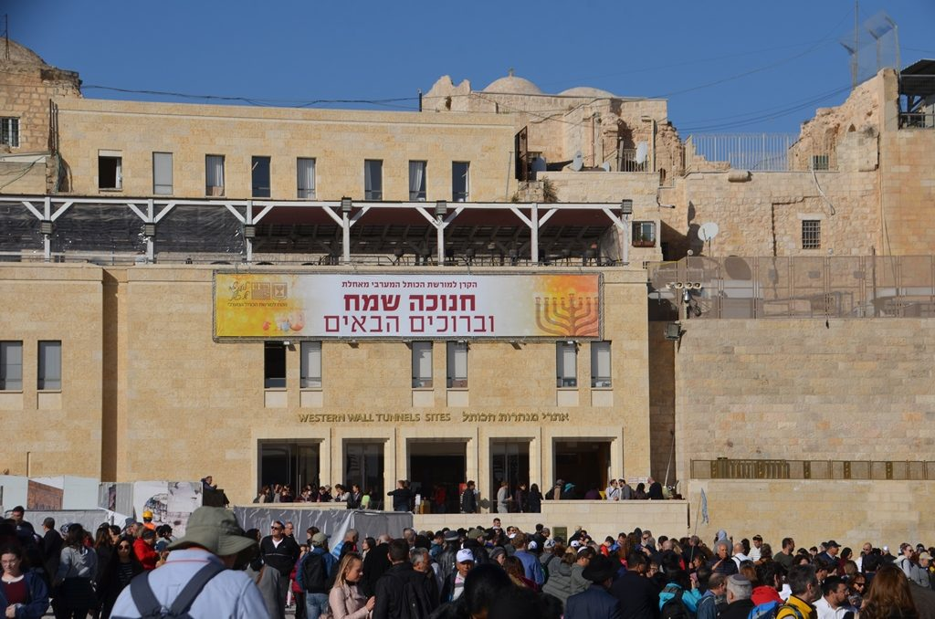 Kotel Plaza on Hanuka with crowd and sign on Western Wall building