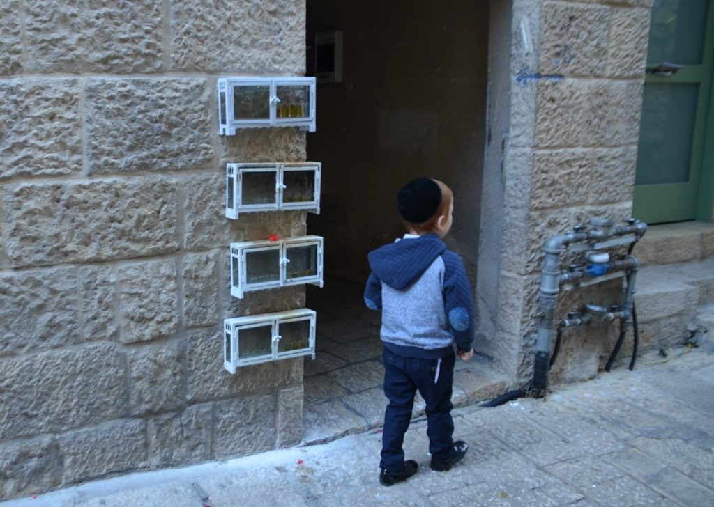 Jerusalem Old City on Hanuka street with four hanukiot on wall as boy walks past