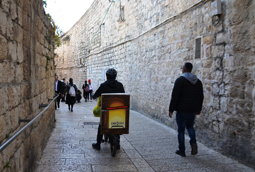 Jerusalem Old City man on bike with a menorah riding through narrow street