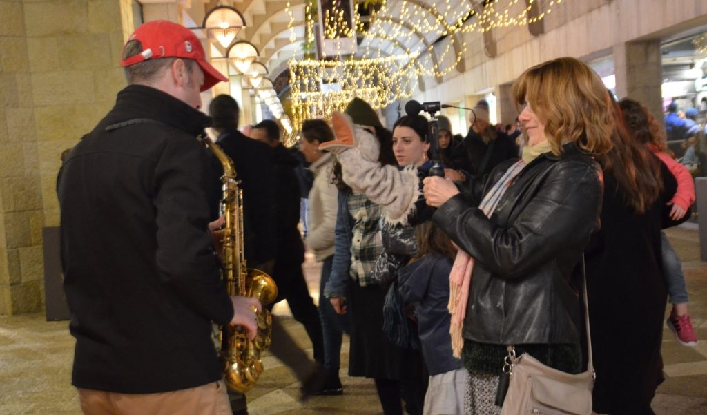 Mamilla Mall on Hanukkah woman with puppet taking video with musician