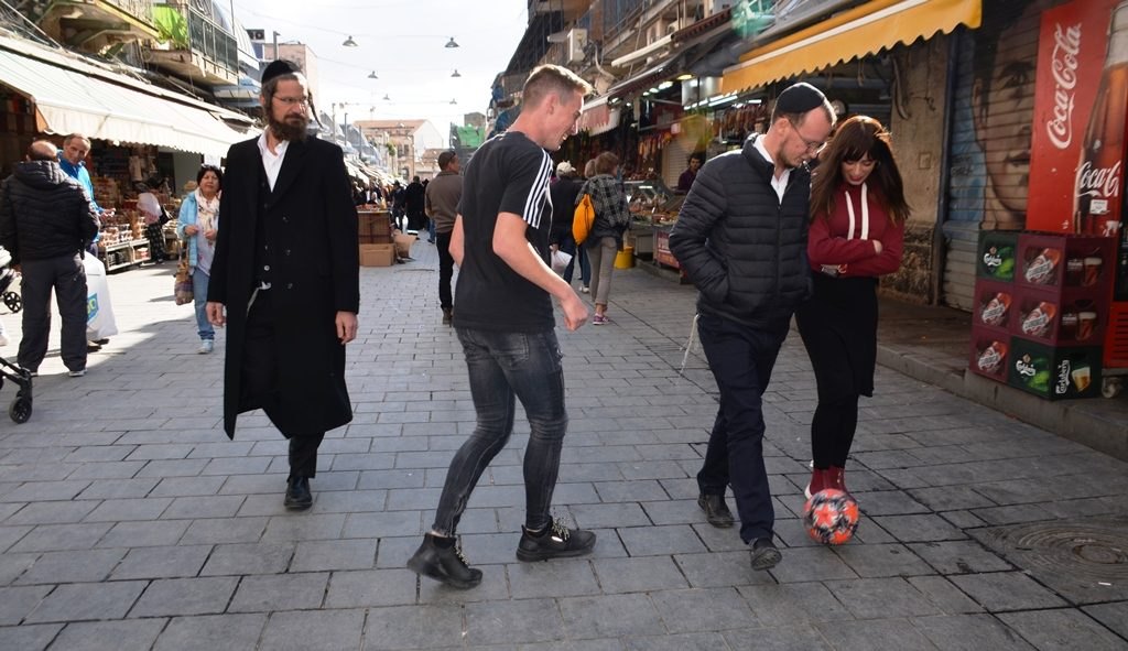 Playing ball in Jerusalem shuk as people walk by