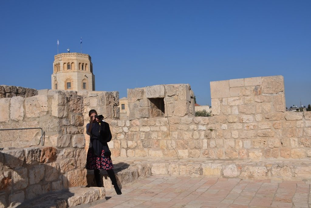 A young woman takes a photo on Stork Tower on Jerusalem Old City Ramparts Path