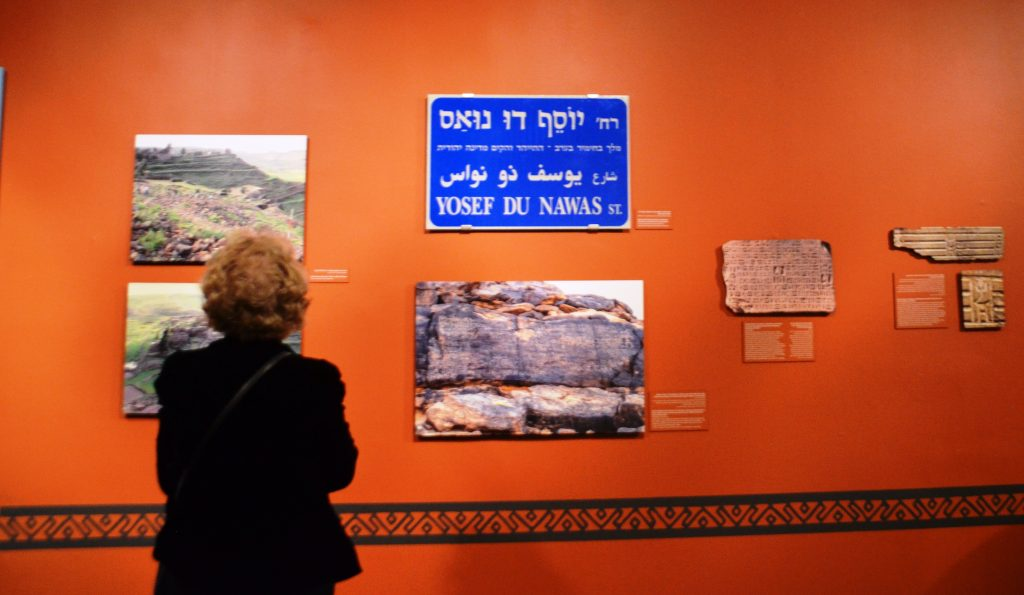 A woman looks at wall display at Bible Lands Museum Jerusalem Yemen exhibit.