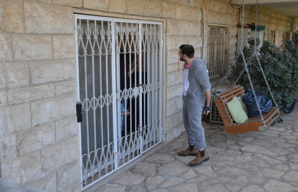 Man in costume visiting family in isolation on Purim in Jerusalem