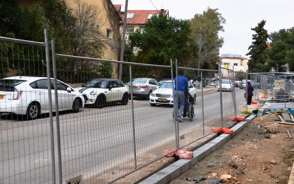 Man pushing wheel chair in Jerusalem street