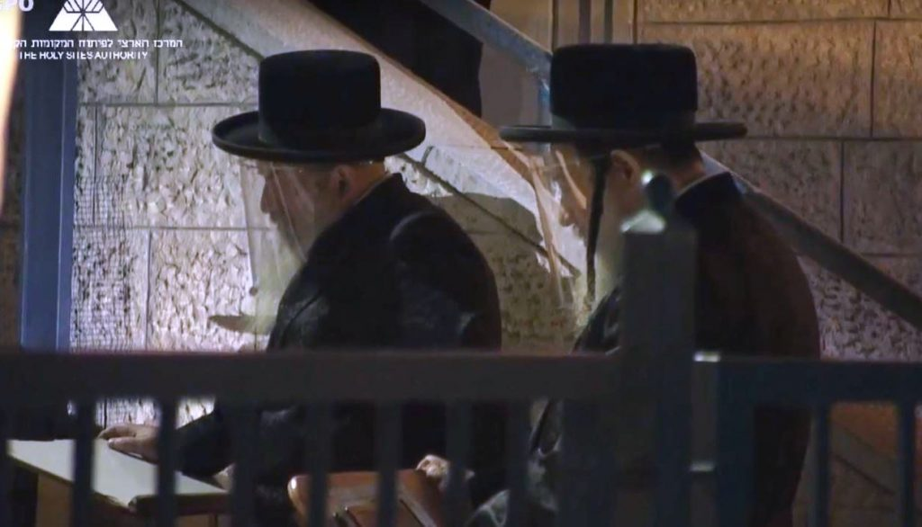 Two Haredi men wearing hats and face shields COVID19
