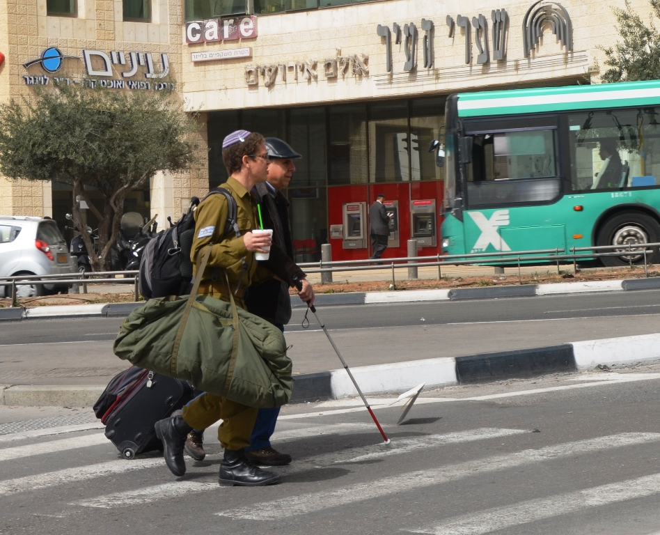 IDF Soldier helps man with a blind walking stick across busy Jerusalem intersections