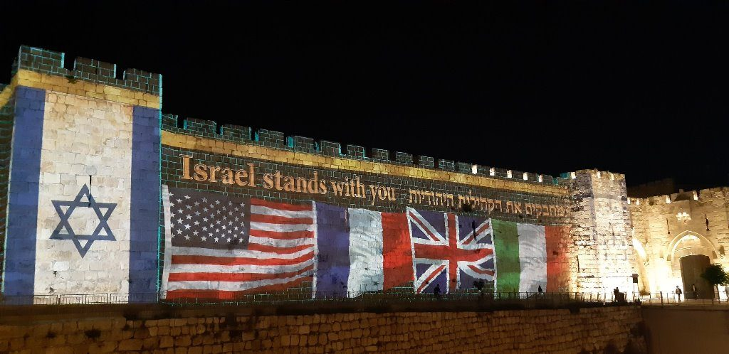 Walls of Old City Jerusalem Israel light with flags and we stand with you COVID-19