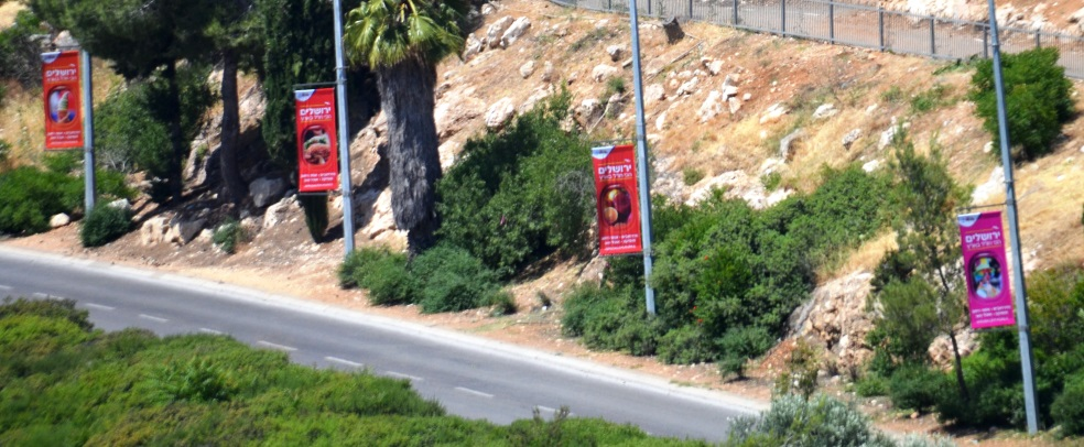 Signs in Jerusalem for summer tourists to come to city instead of going overseas vacations