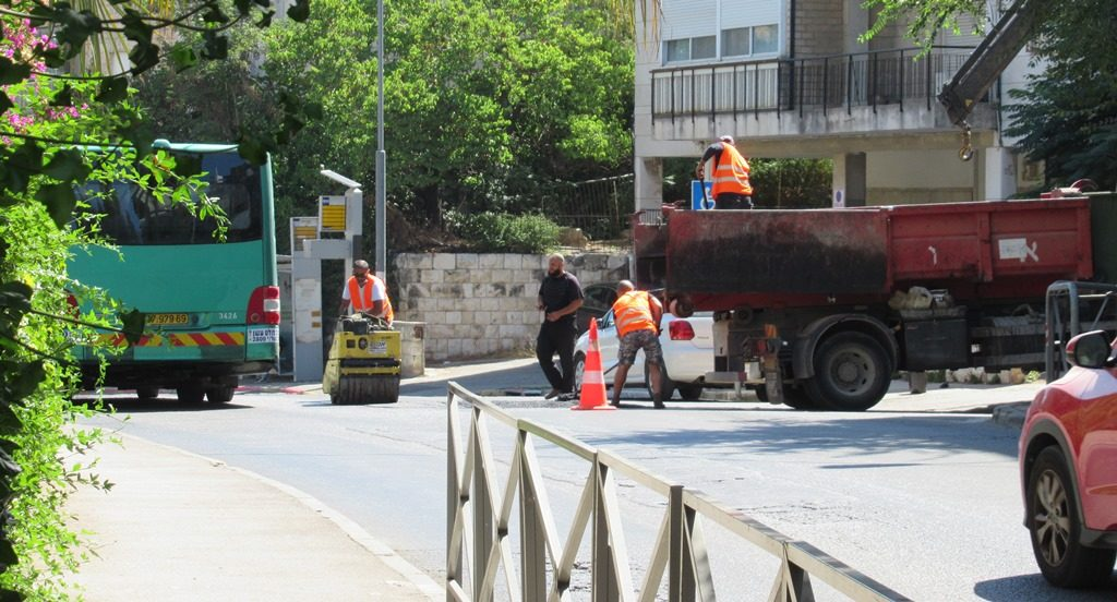 Workers in Jerusalem filling a pot hole in street