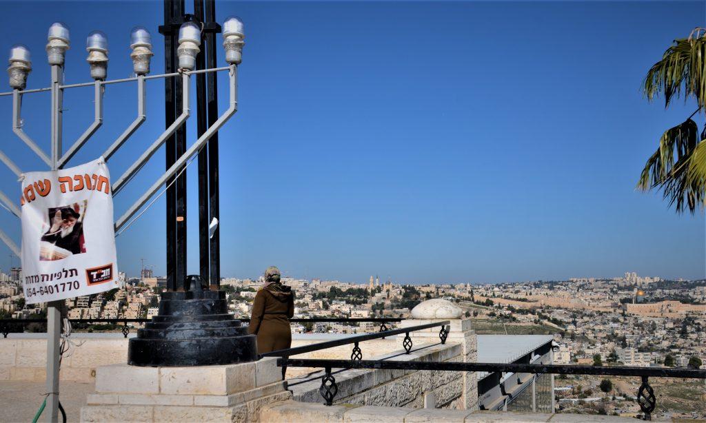 Tayelet scene Muslim woman  near Hanukkah menorah